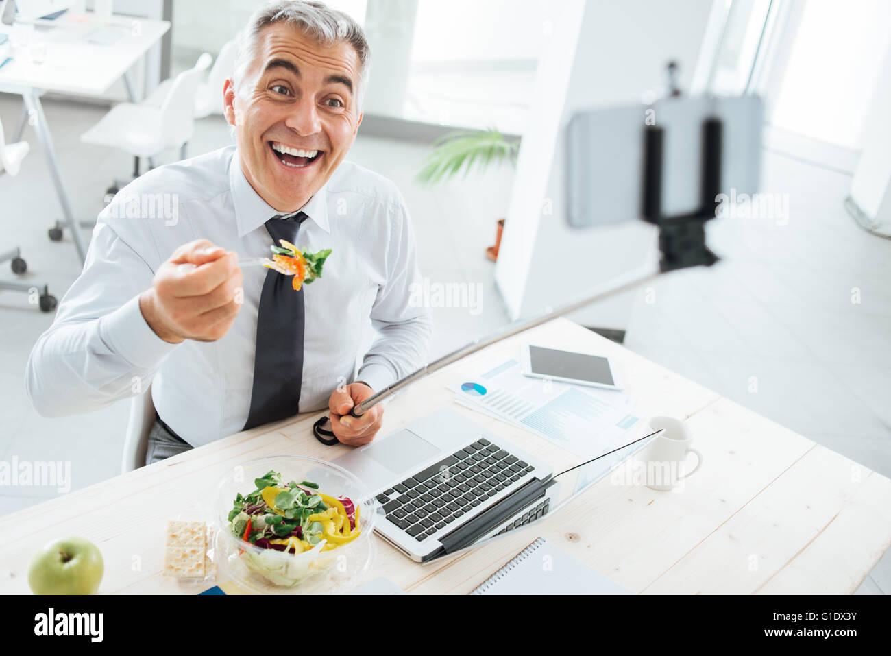 Happy smiling businessman at office 24 avoir une pause déjeuner et prendre des autoportraits avec un bâton Photo Stock