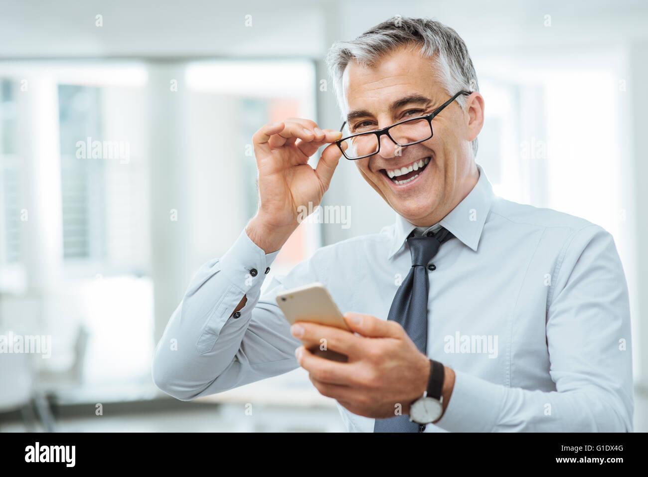 Smiling businessman with vision des problèmes, il s'ajuste ses lunettes et lire quelque chose sur son téléphone Photo Stock