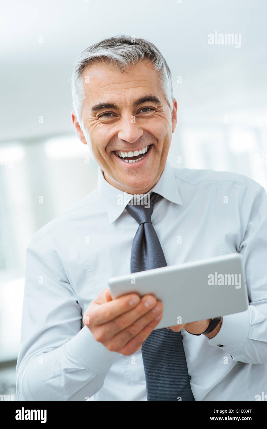 Smiling confident businessman looking at camera et à l'aide d'un écran tactile numérique Photo Stock