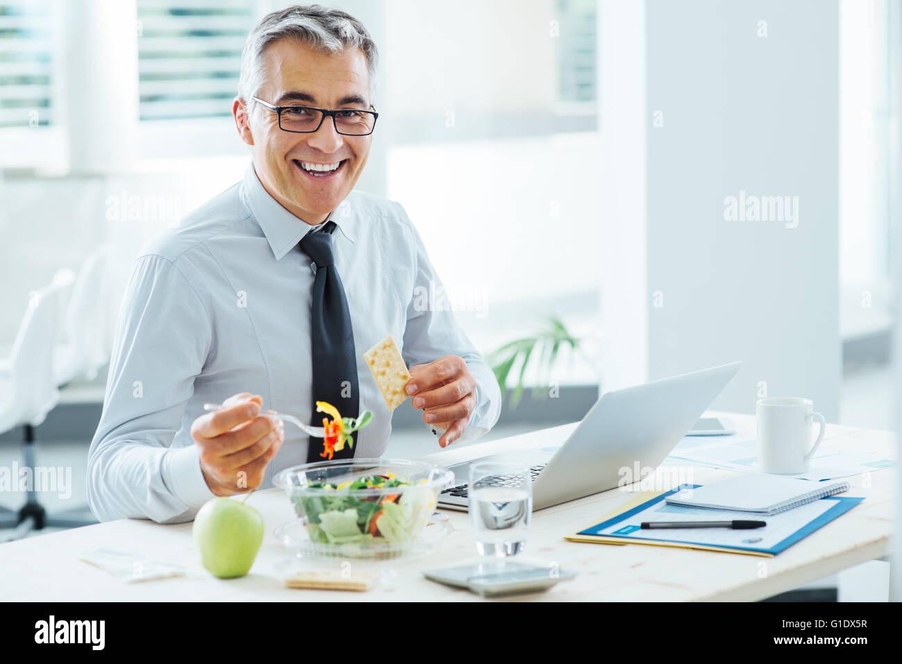 Smiling businessman sitting at Office 24 et avoir une pause déjeuner, il est en train de manger un saladier Photo Stock