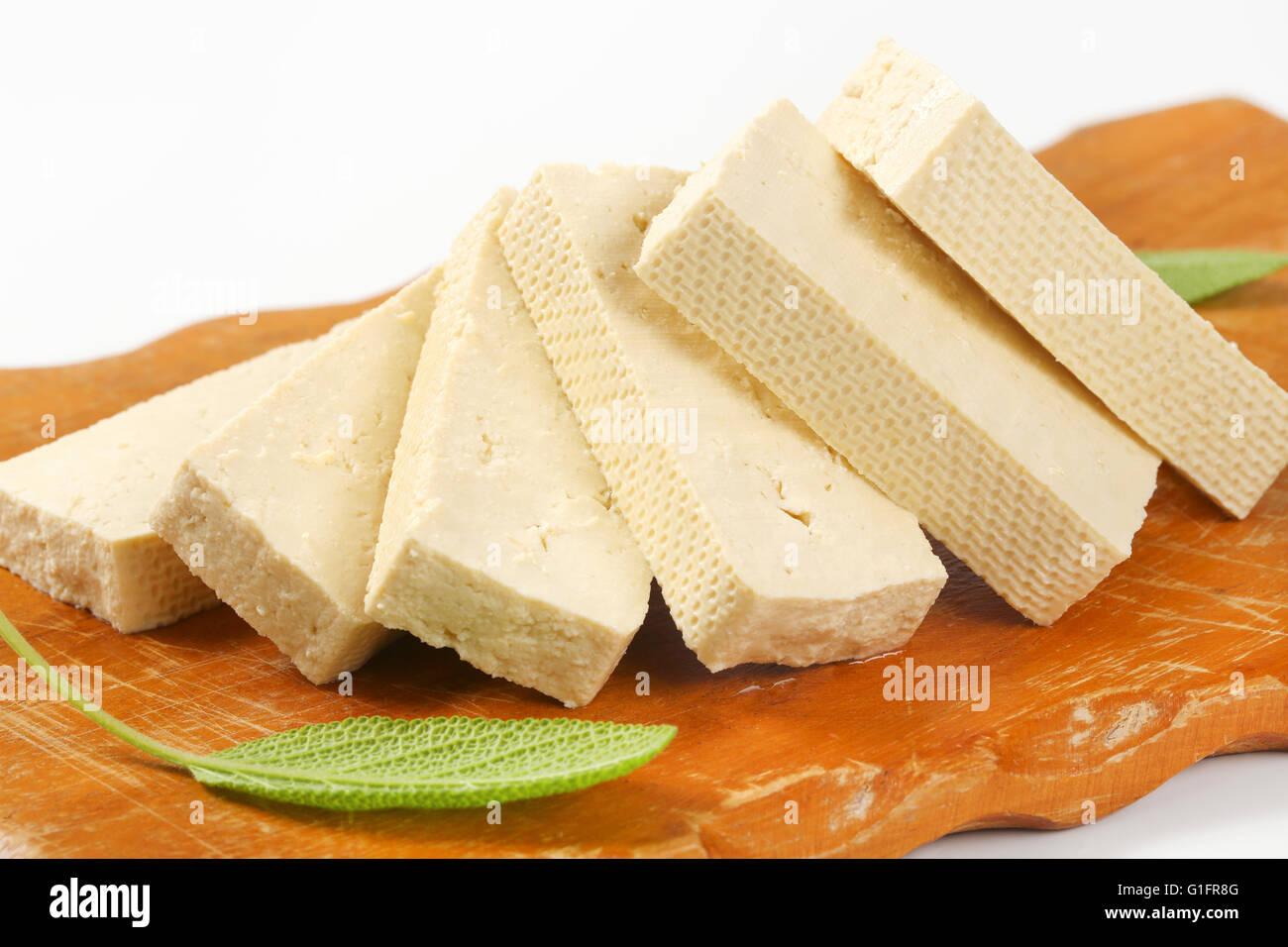 Bloc de tofu frais en tranches sur une planche à découper Photo Stock