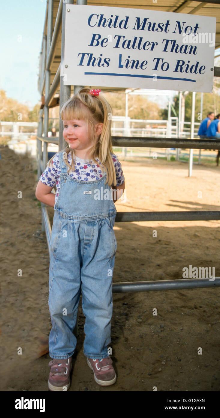 3 ans, fille, et contrôle de signer pour la hauteur de qualification ride poney.©Myrleen Pearson Photo Stock