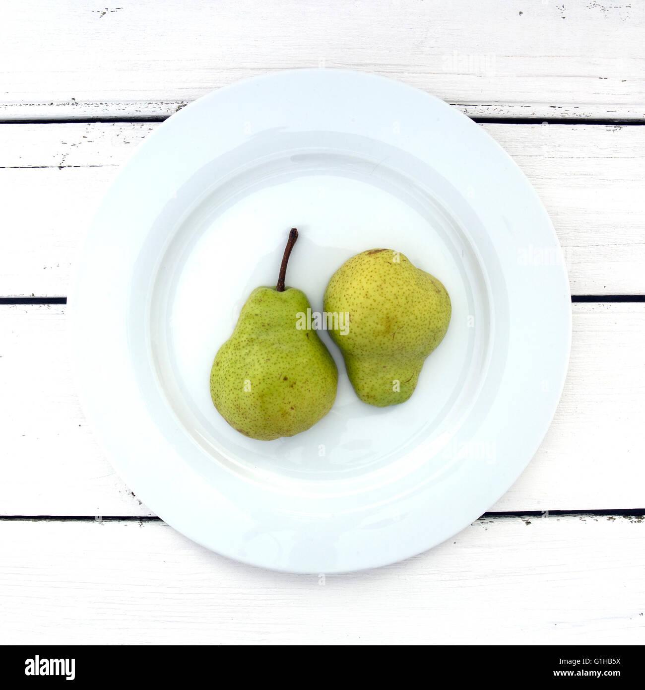 Les deux demi-poire sur une assiette blanche sur un fond de bois blanc rétro Photo Stock