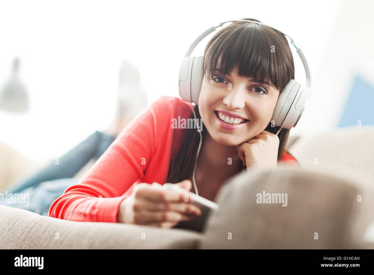 Smiling young woman relaxing at home sur le canapé, elle porte un casque, à l'aide d'une tablette Photo Stock