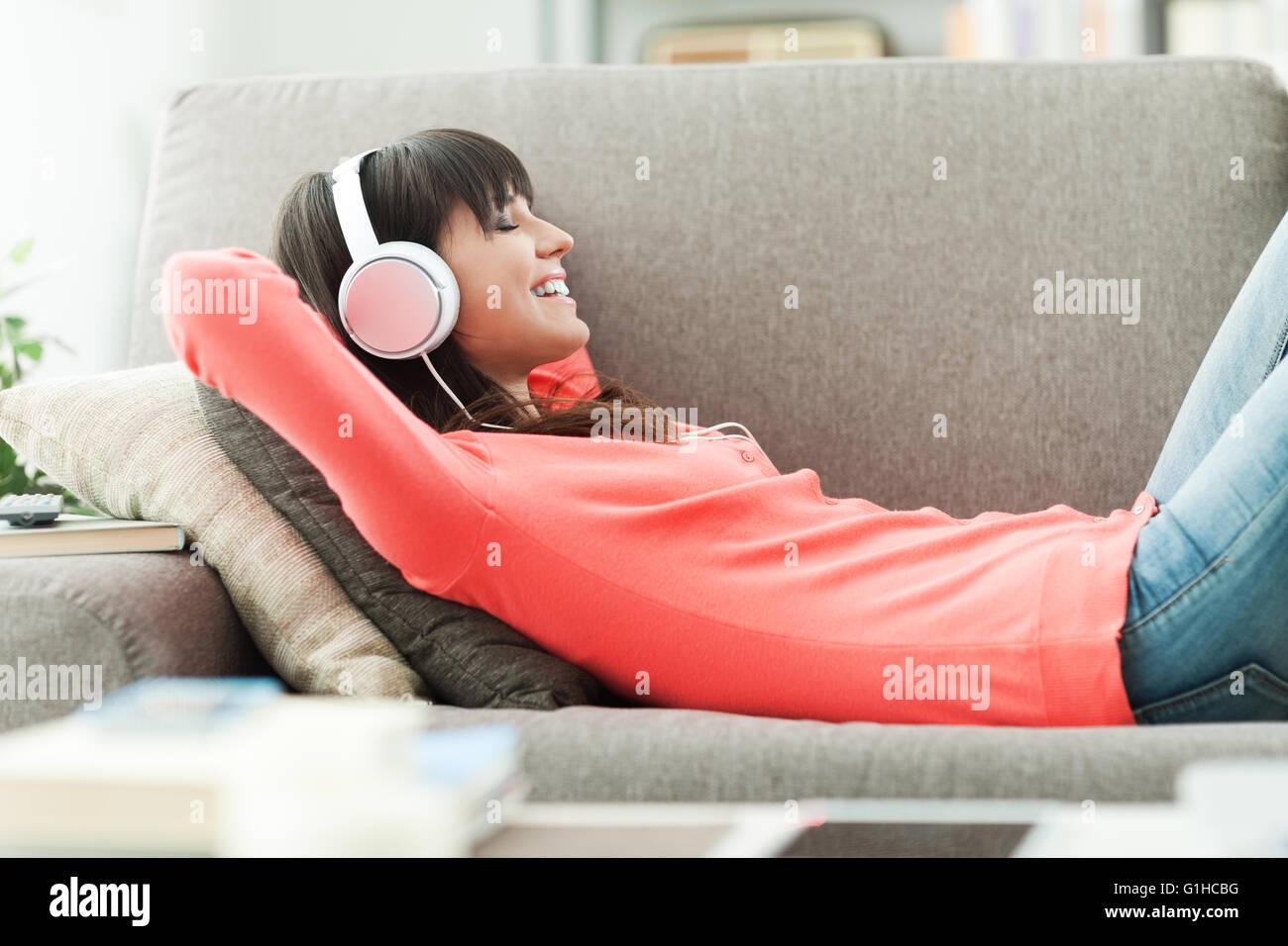 Jeune femme séduisante de détente sur le canapé à la maison, elle est à l'écoute de la musique avec des écouteurs Banque D'Images