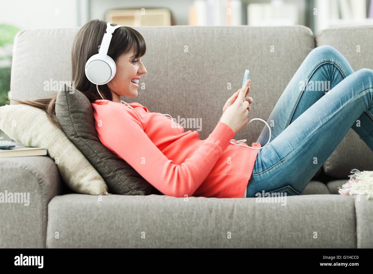 Belle jeune femme sur le canapé à la maison, elle joue de la musique avec son smartphone et portant des Photo Stock