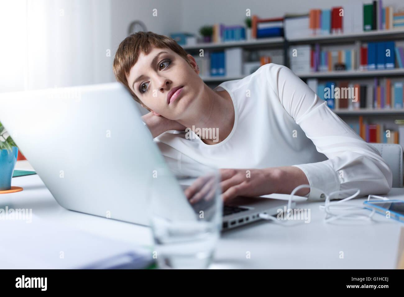 Femme fatiguée dans le bureau s'appuyant sur sa main en utilisant un ordinateur portable Photo Stock