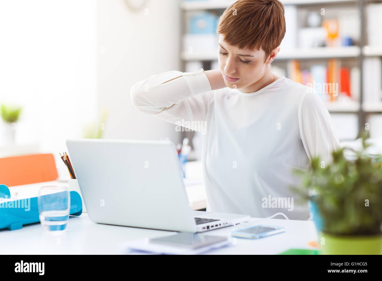 Office worker sitting at desk et toucher le dos, elle a une douleur au cou Photo Stock