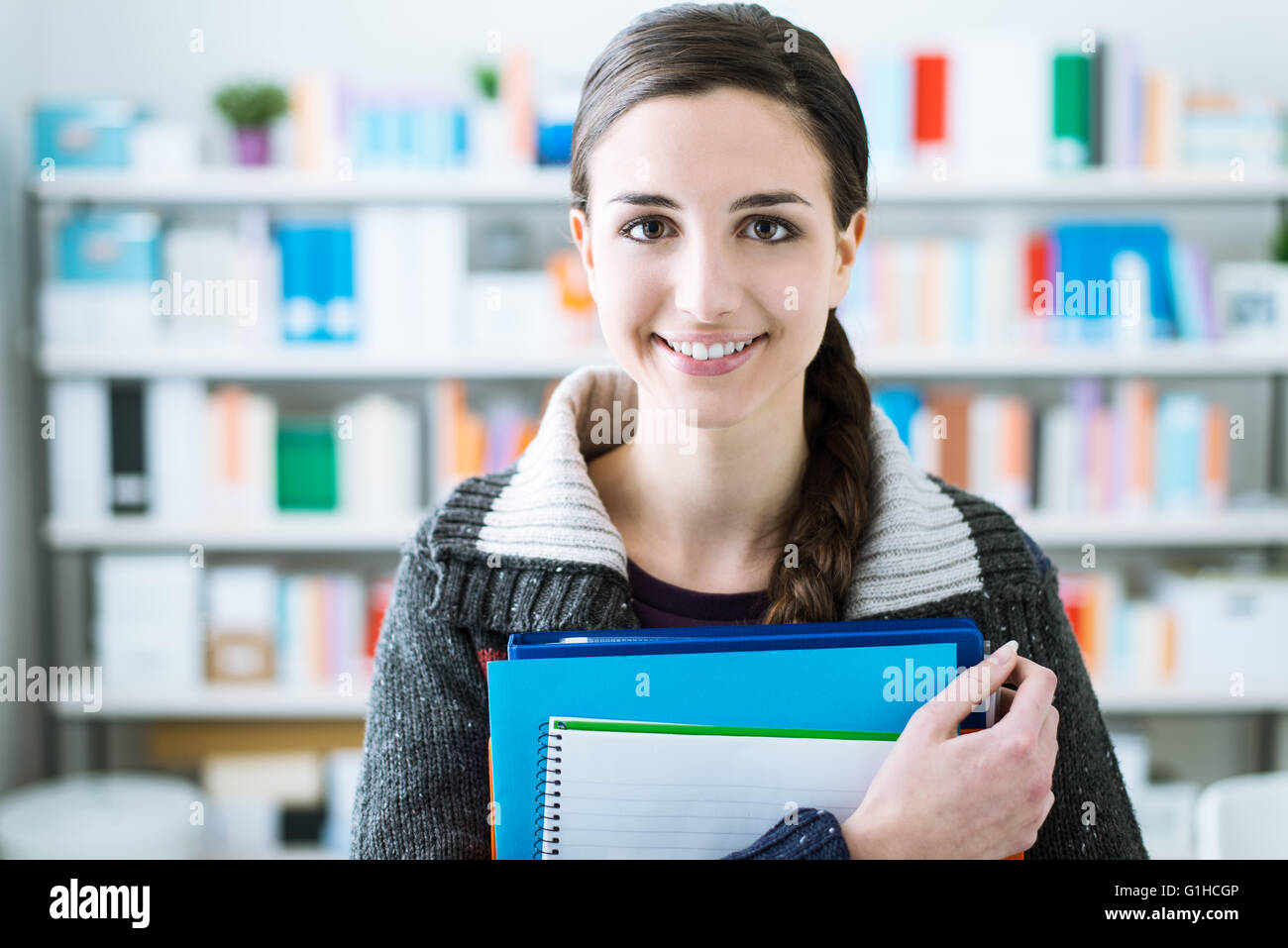 Jeune étudiante souriante jeune fille dans la bibliothèque de l'école, elle est holding notebooks Photo Stock