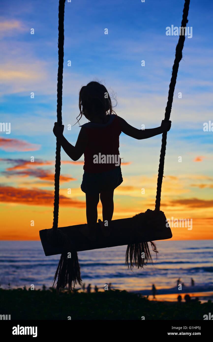 Silhouette noire de happy baby girl de haut vol avec plaisir sur swing sur ocean beach surf et bleu orange fond Photo Stock