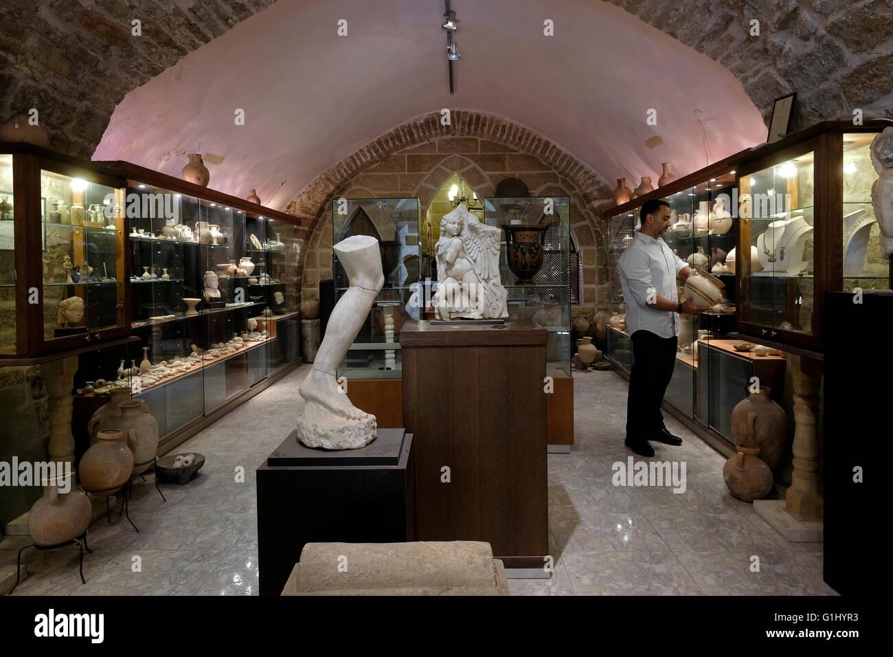 L'antiquité Alan Baidun concessionnaire inspection une ancienne question à son magasin situé Photo Stock