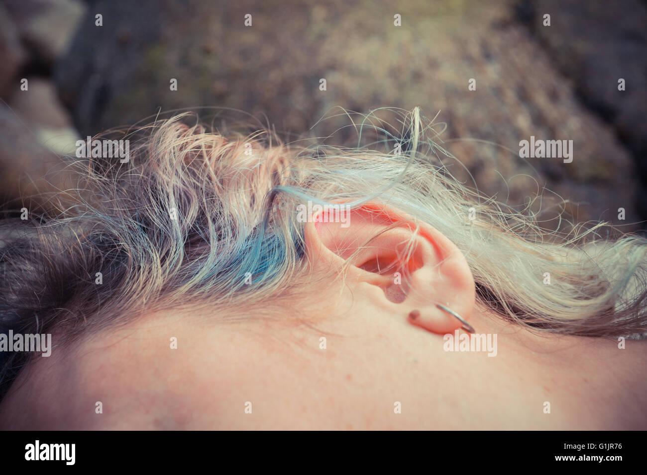 Gros plan sur l'oreille d'une jeune femme comme elle est situé à l'extérieur Photo Stock