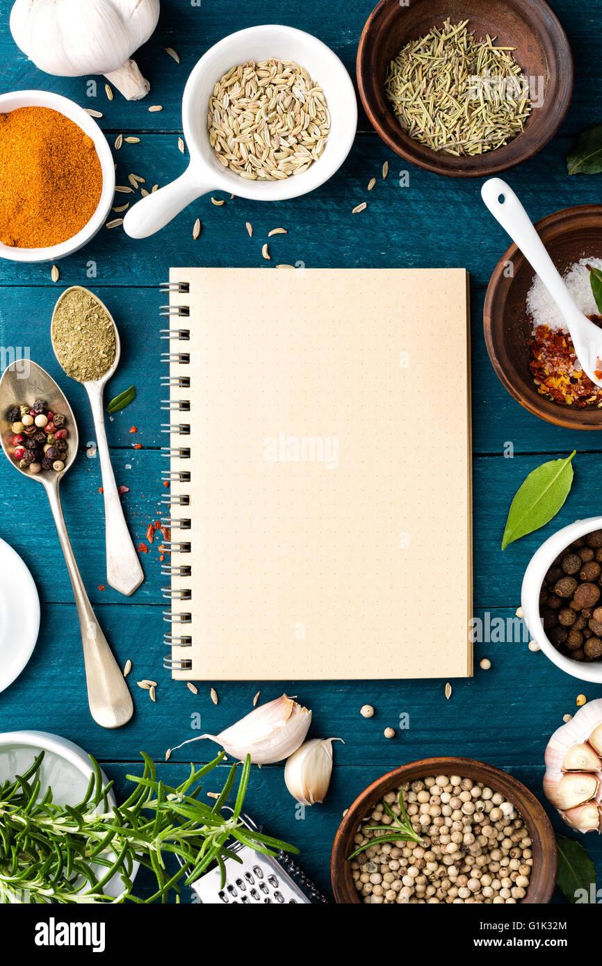 Arrière-plan et livre de recettes culinaires avec épices diverses sur le tableau en bois Photo Stock