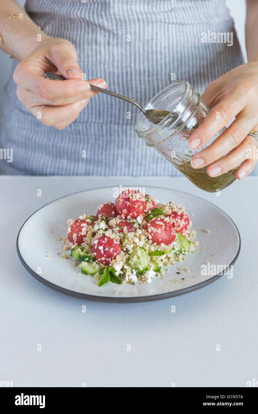 Une femme gettitng est prêt à arroser une pastèque salade de boulgour au citron vert et miel vinaigrette. Photo Stock