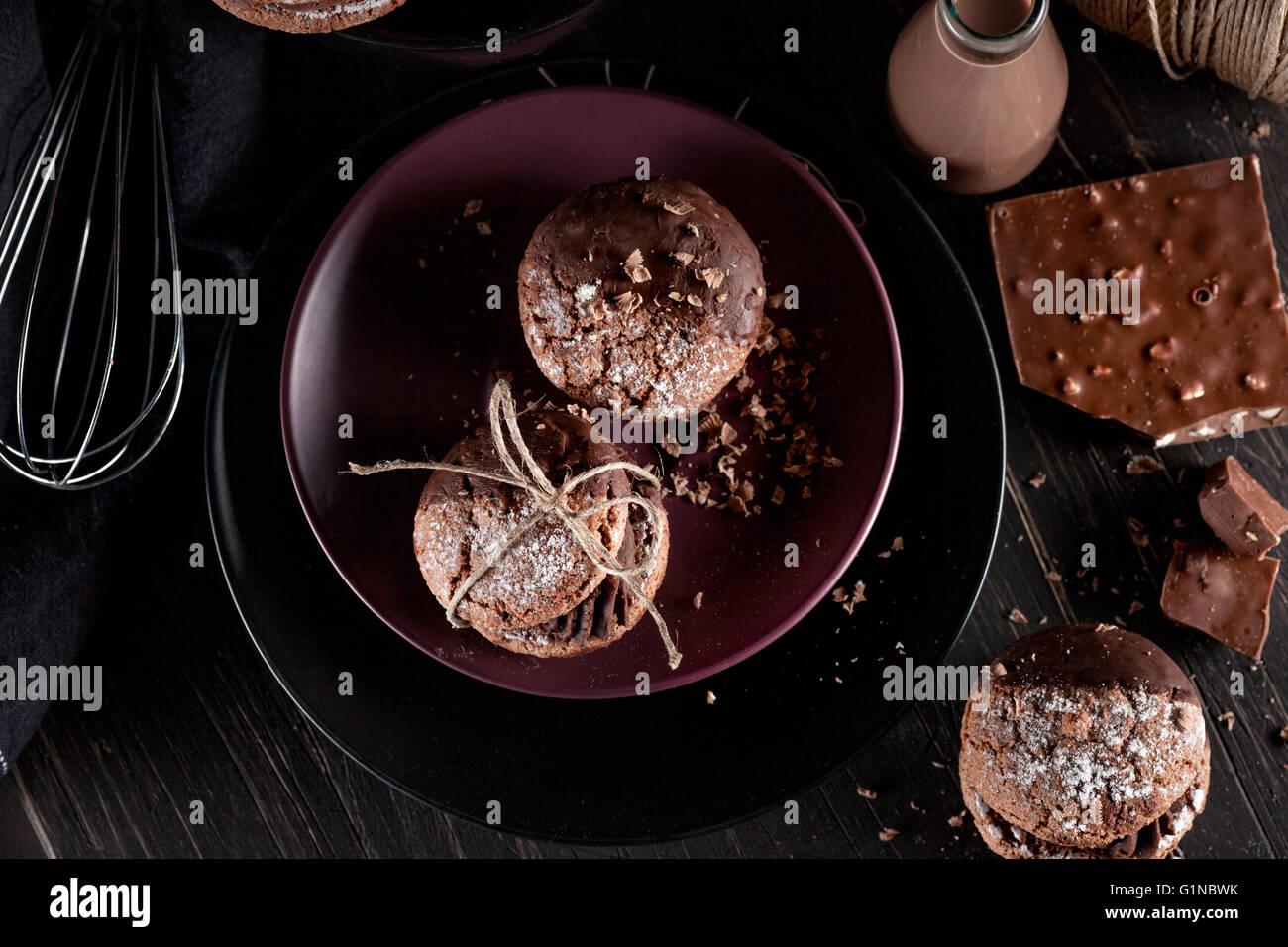 L'Italien maroni les cookies sur la plaque de chocolat et des milkshakes, tissu, ordinateur portable sur dark Photo Stock