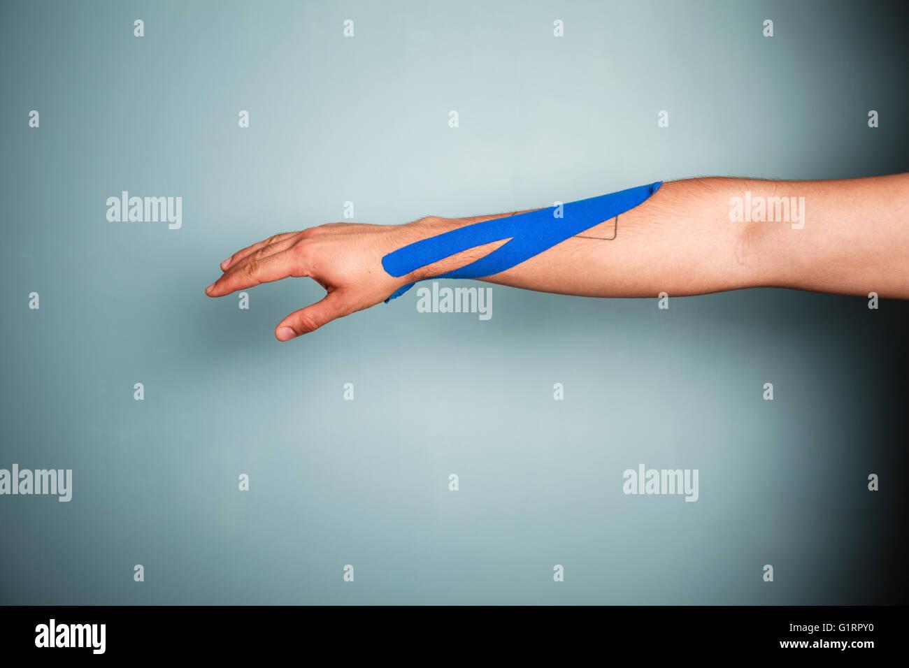 Le bras d'un homme avec du ruban kinesio sur elle Photo Stock