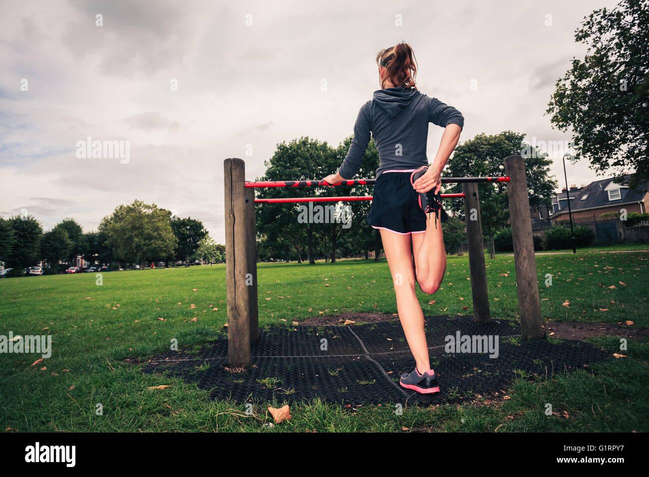 Une jeune femme s'étire ses jambes sur l'équipement de conditionnement physique dans le parc Photo Stock