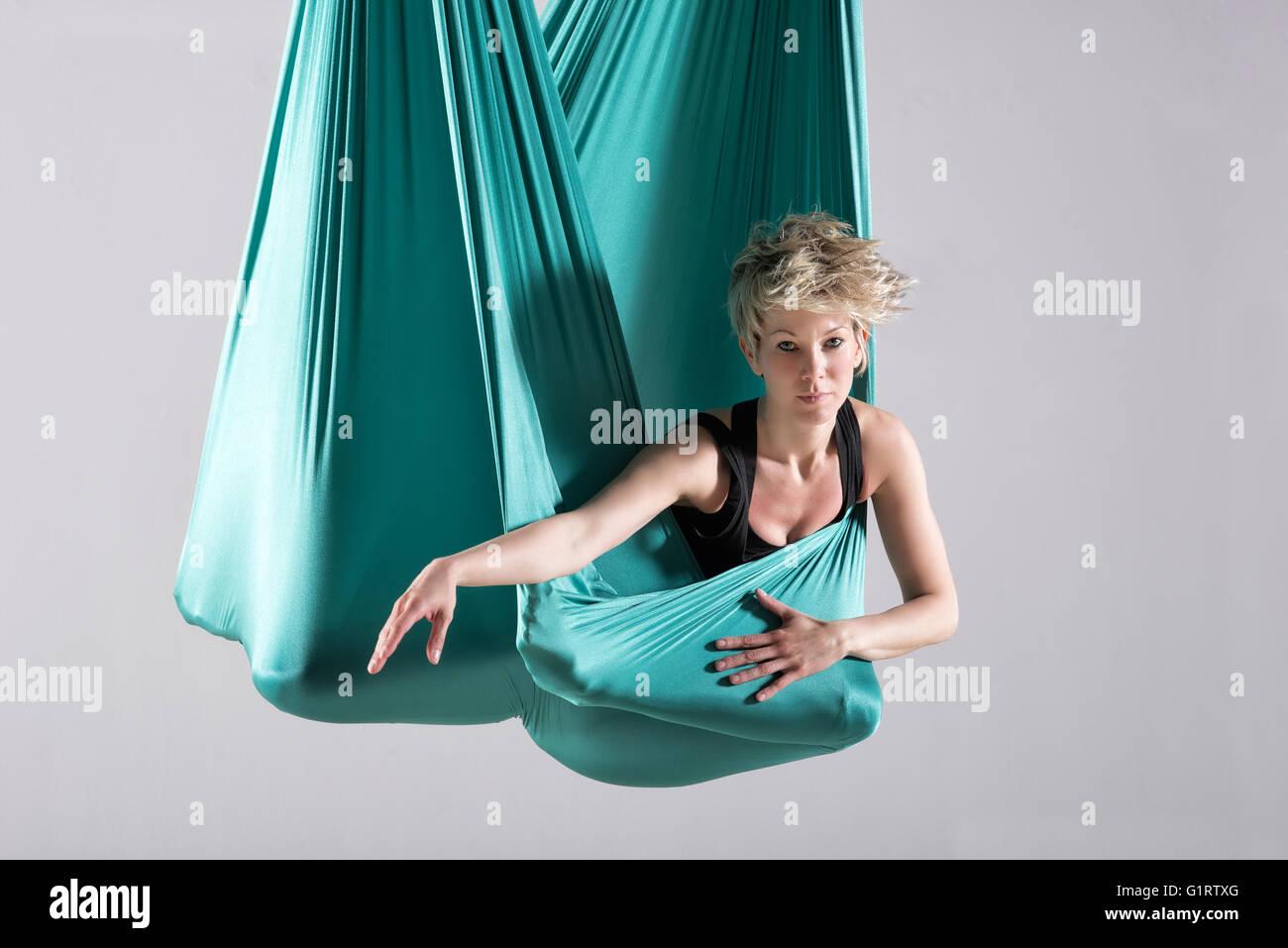 Seule femme athlétique intense faisant des exercices d'étirement de la jambe et de la hanche enveloppé Photo Stock