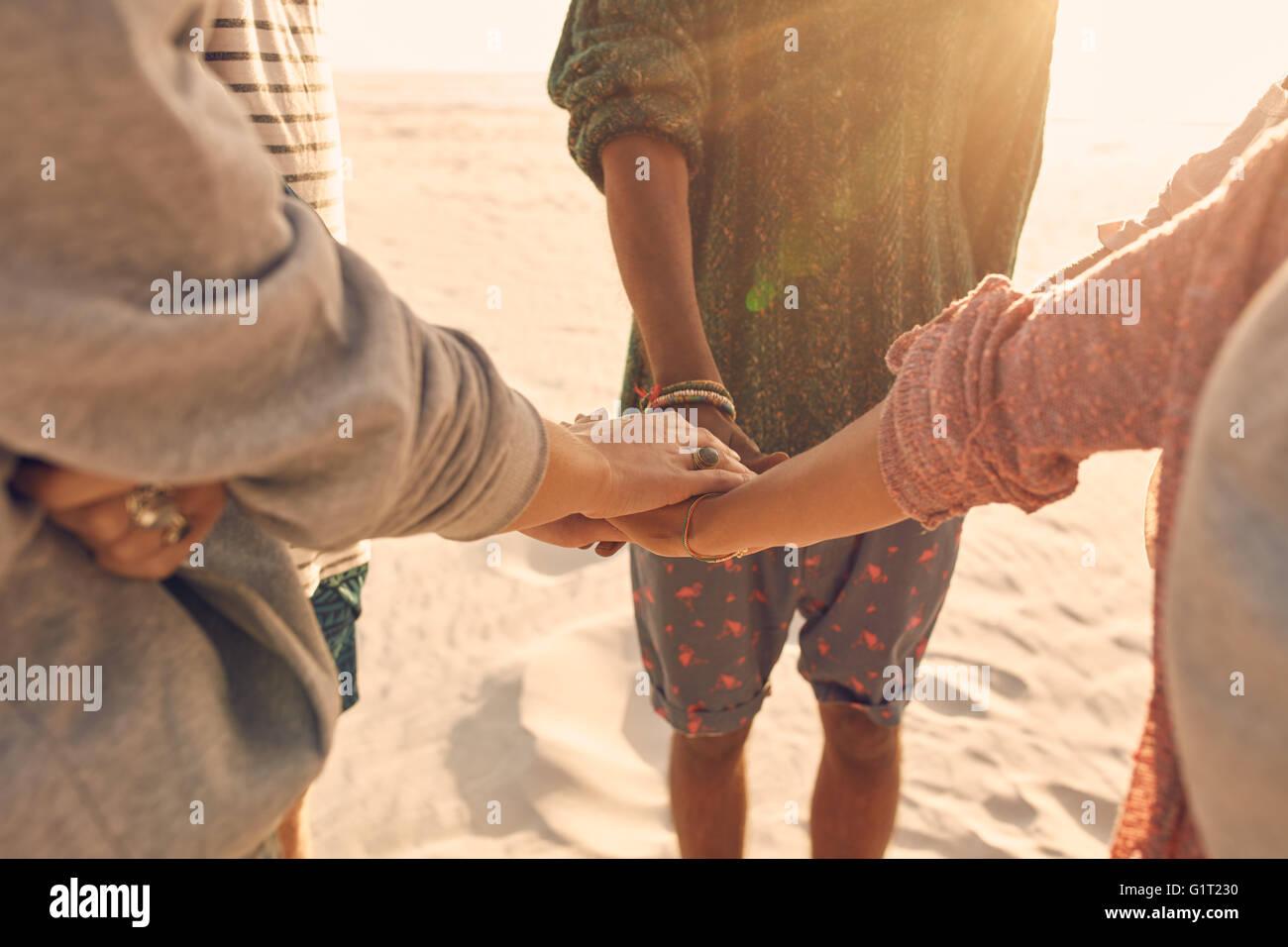Groupe d'amis leur pile les mains ensemble. Les jeunes hommes et femmes se tenant ensemble à la plage, les mains Banque D'Images
