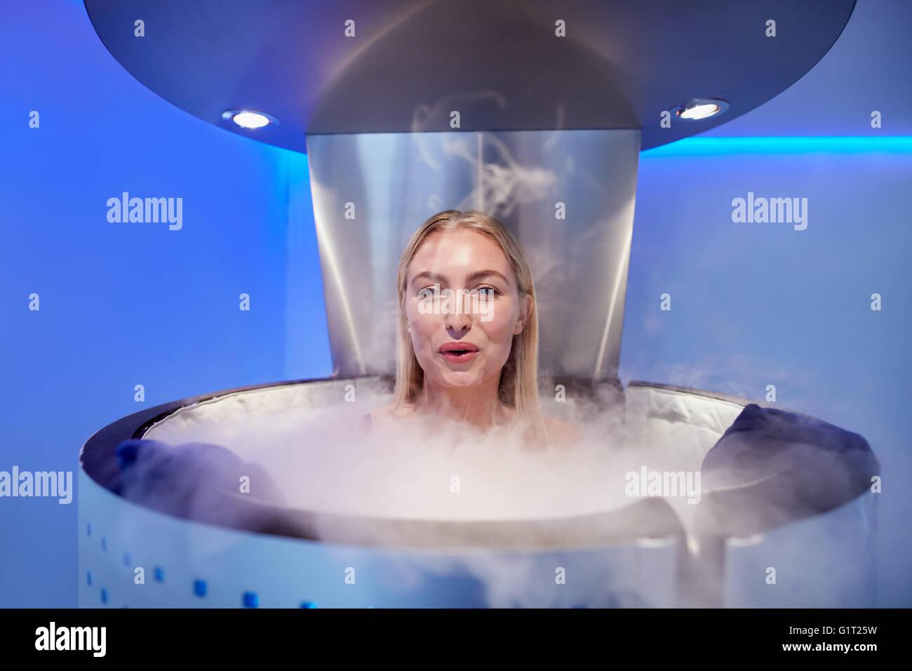 Portrait de jeune femme dans un corps tout entier la cryothérapie cabine. Elle est à la recherche à Photo Stock