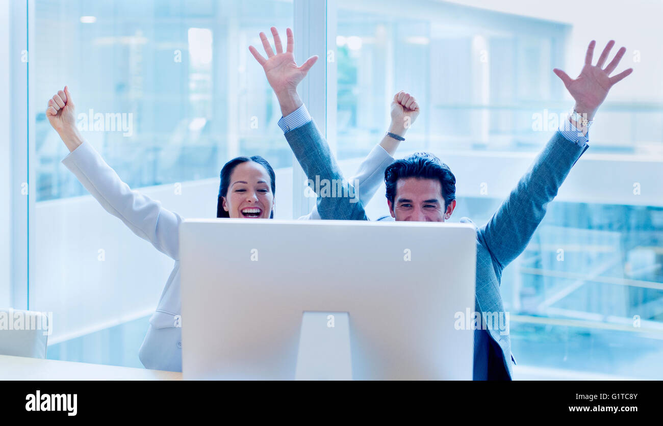 Exubérant businessman and businesswoman cheering with arms raised at computer in office Banque D'Images