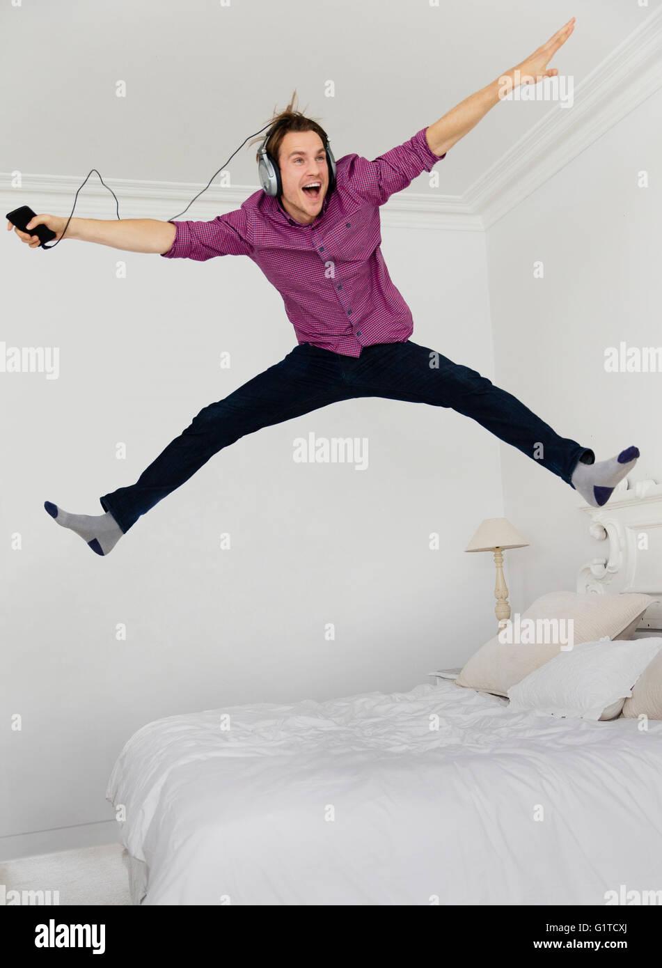 Homme ludique de sauter sur le lit avec les jambes écartées à l'écoute de la musique avec Photo Stock