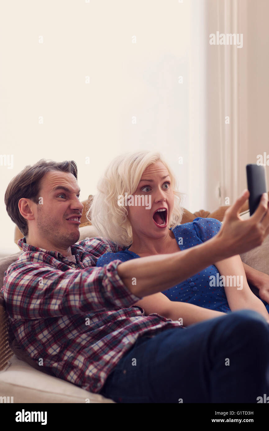 Playful couple making faces selfies en tenant Banque D'Images