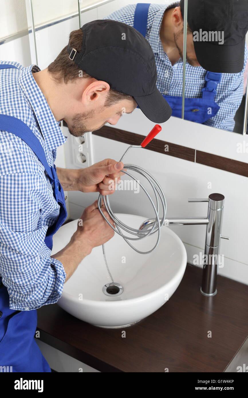 Un plombier Nettoyage d'une vidange du tuyau avec une spirale Photo Stock