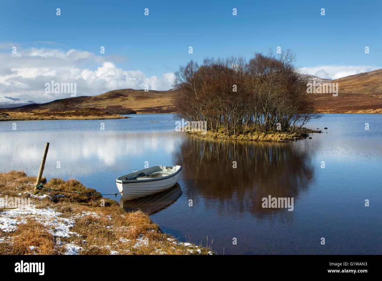 Bateau blanc amarré dans un petit Loch Photo Stock