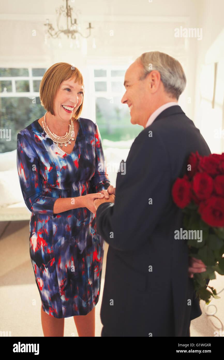 Bien-habillé mari surprenant femme avec bouquet de rose Photo Stock