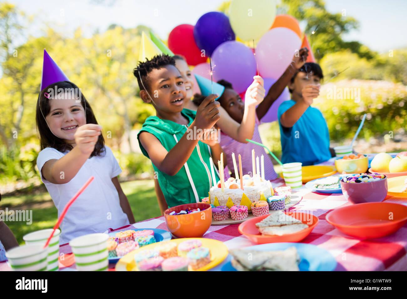 Mignon enfants sourire et s'amuser pendant une soirée d'anniversaire Photo Stock
