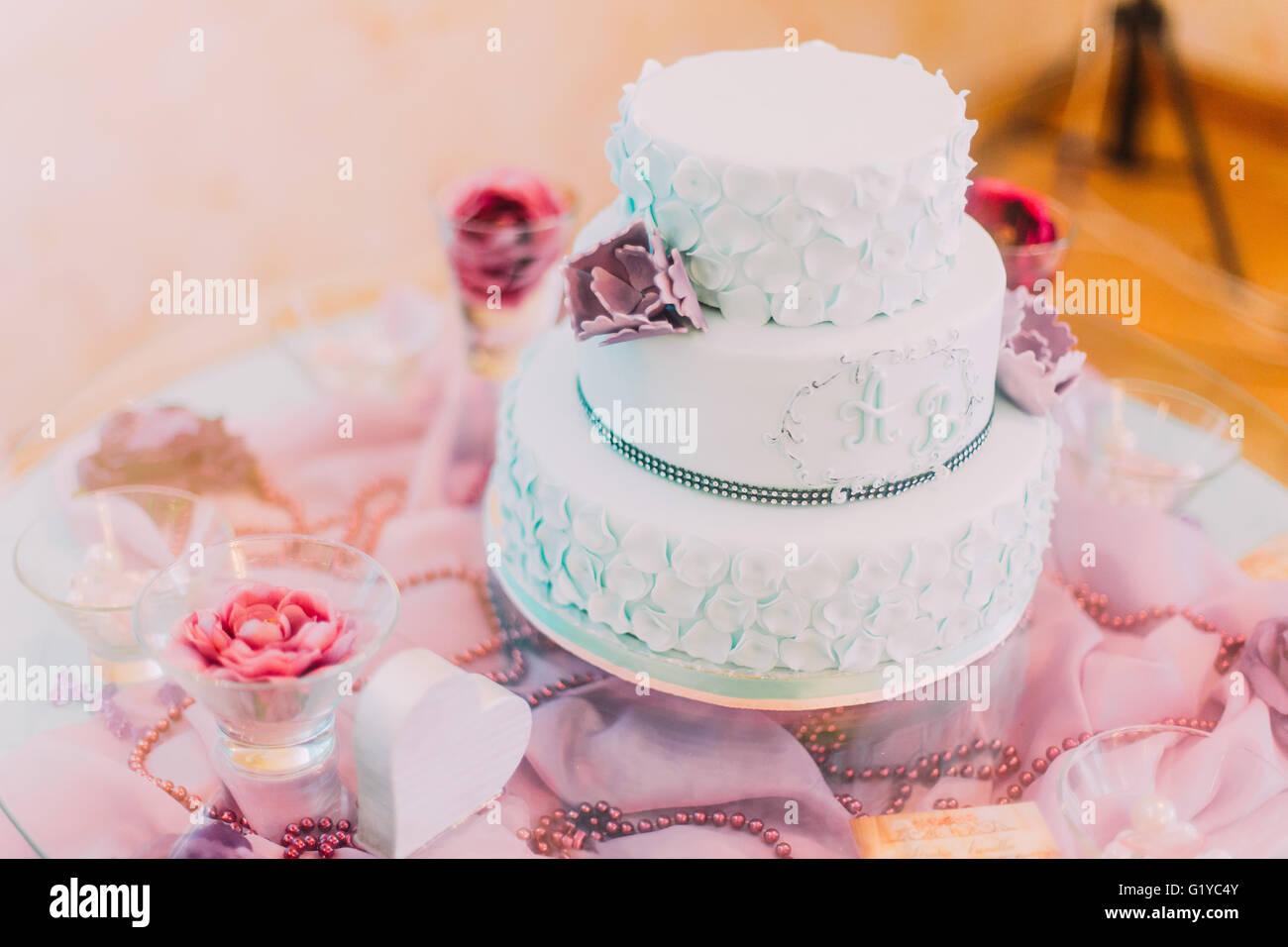 Gâteau de mariage bleu et blanc décoré de fleurs violettes Photo Stock