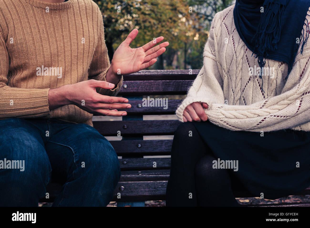 Un jeune homme et femme sont assis sur un banc de parc et à discuter Photo Stock