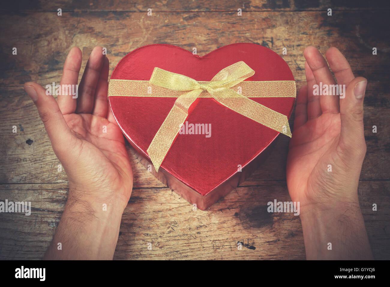Un homme a les mains en appui sur une surface en bois avec une boîte en forme de coeur Photo Stock