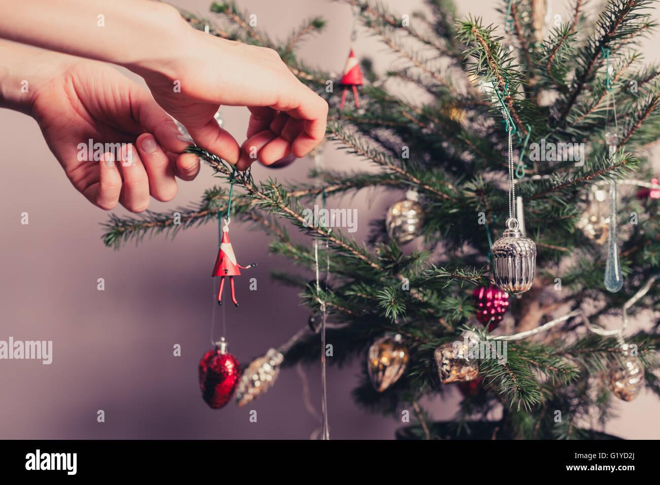 Mains décorer un arbre de Noël avec toutes sortes de choses colorées Photo Stock