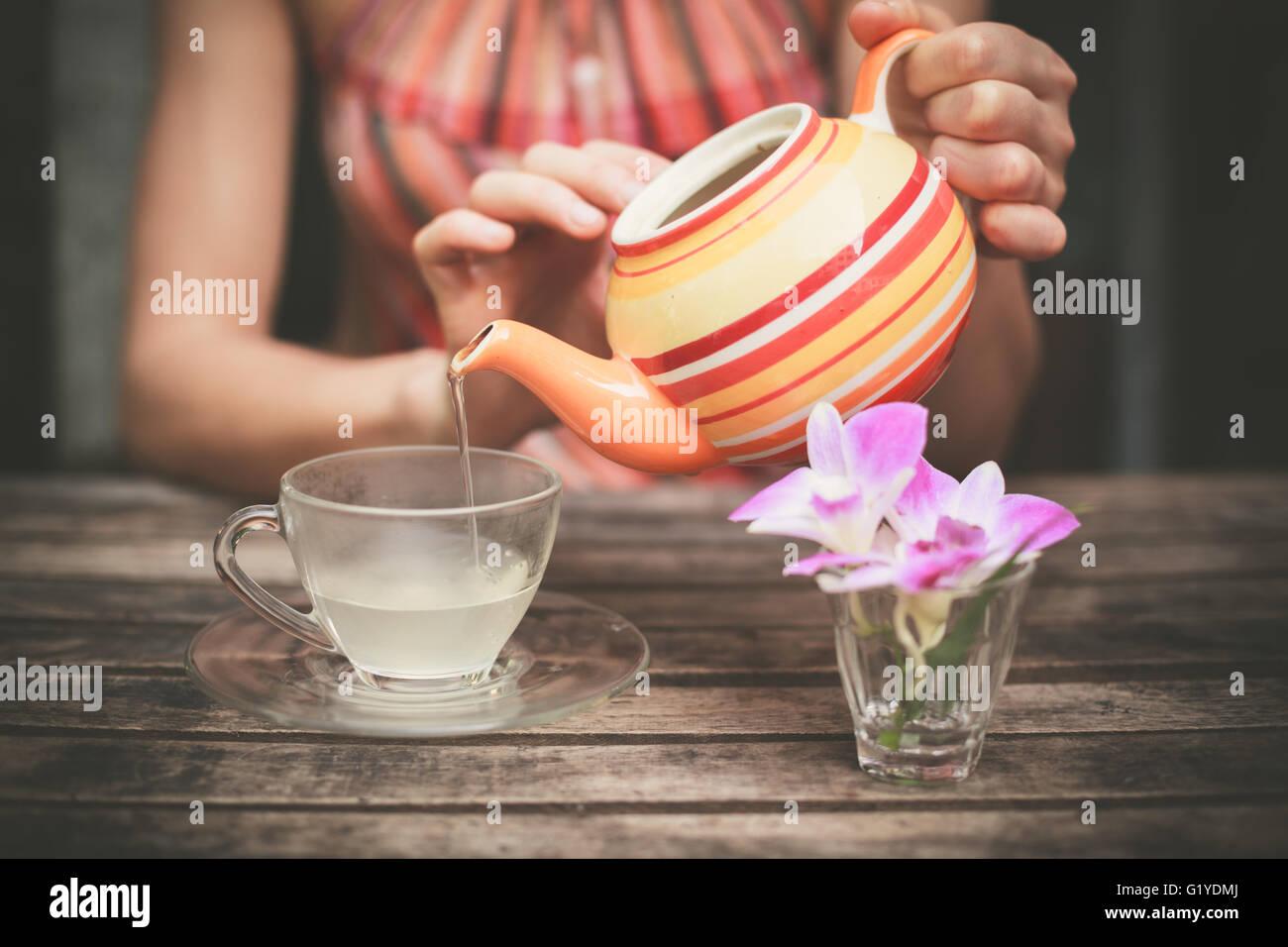 Une jeune femme est assise à une table et verse une tasse de thé Photo Stock