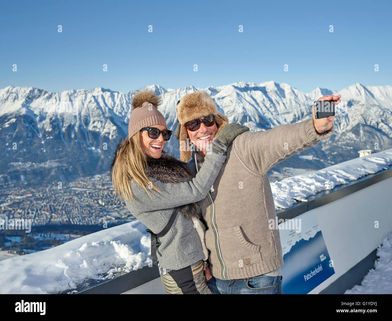 Couple photographing themselves, faisant un en face de selfies paysages de montagne, Patscherkofel, Patsch, chaîne Photo Stock