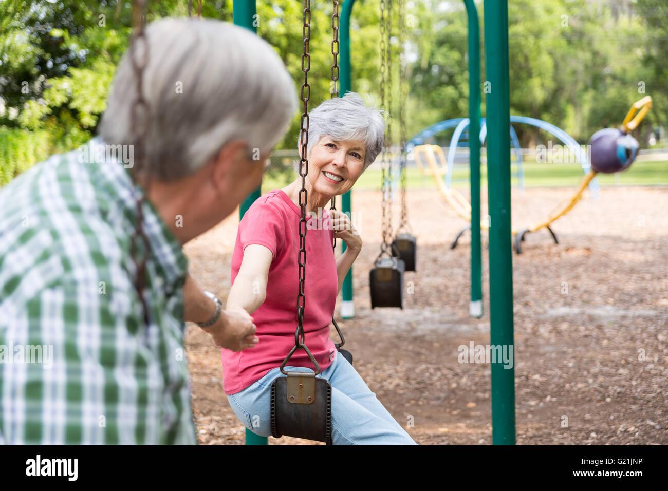 Senior Couple Holding hands on balançant dans le parc Photo Stock