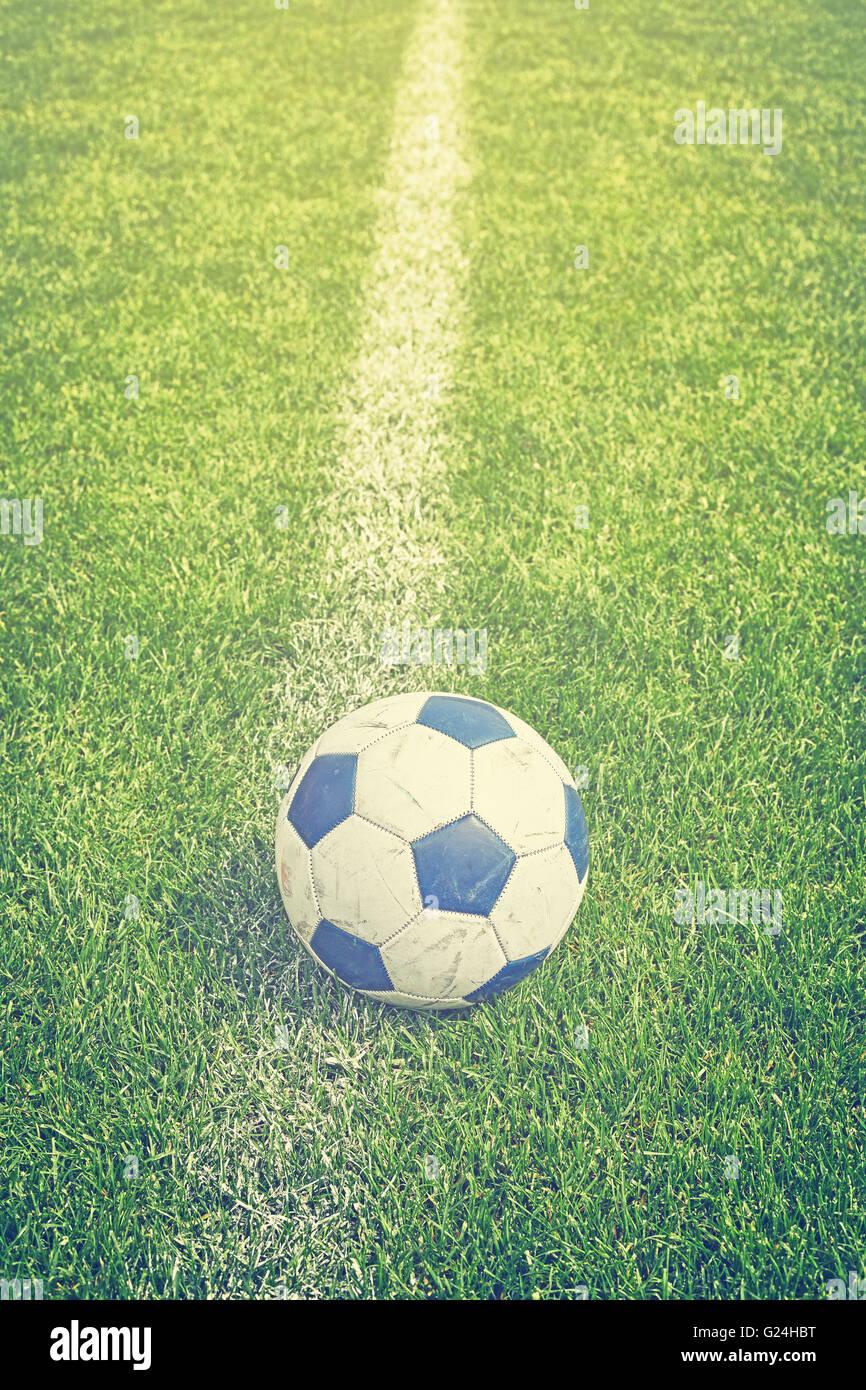 Retro photo aux couleurs d'un ballon de soccer sur l'herbe par touche, faible profondeur de champ. Photo Stock