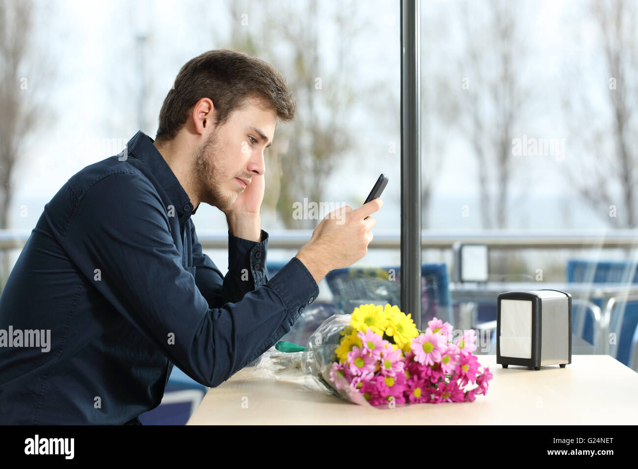 Homme triste avec un bouquet de fleurs a pris la parole à une date phone messages dans un café Photo Stock
