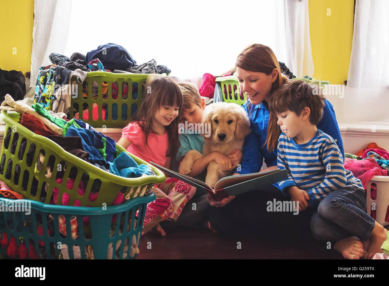 Smiling mother lecture à trois enfants et chiot golden retriever dog entouré de paniers à linge Photo Stock