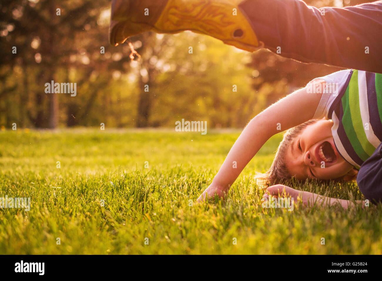 Garçon rire et sur le matériel roulant sur l'herbe dans le jardin Photo Stock