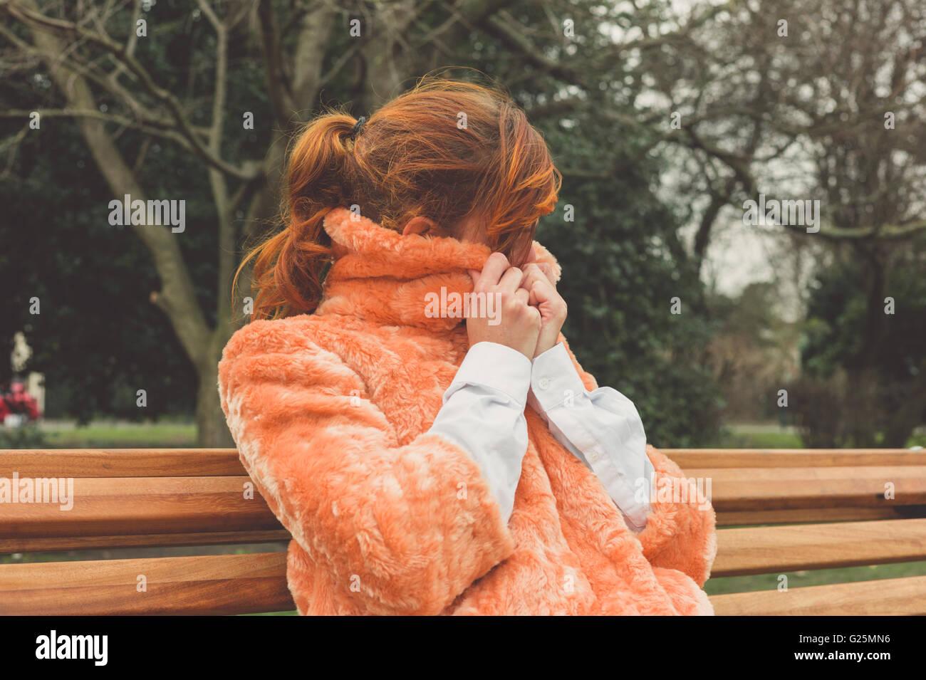 Une jeune femme est assise sur un banc de parc et s'enroule dans son manteau, un jour d'hiver Photo Stock