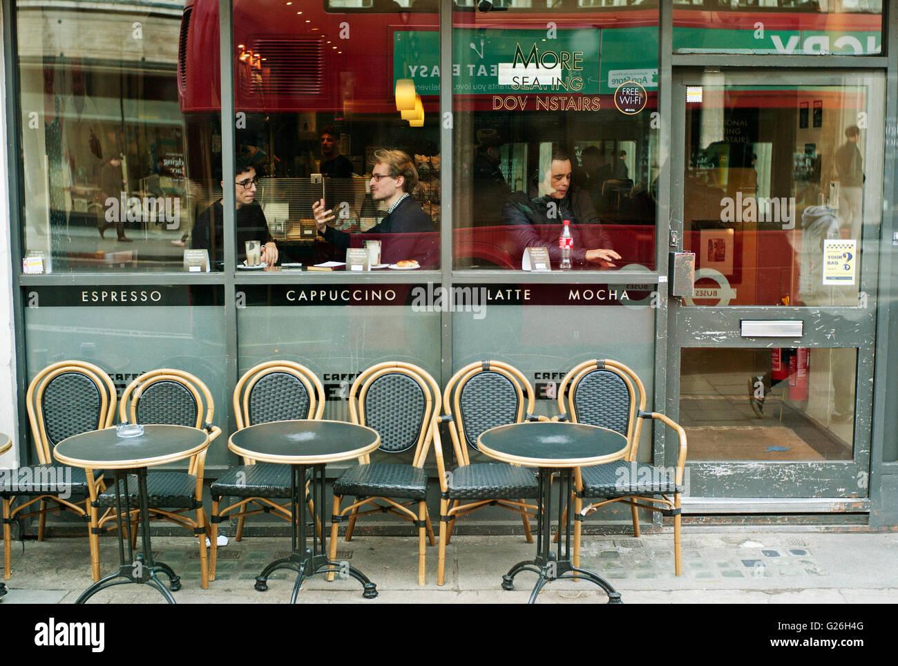 Café avec tables et chaises vides à l'extérieur avec des personnes à l'intérieur à la recherche d'une fenêtre Banque D'Images