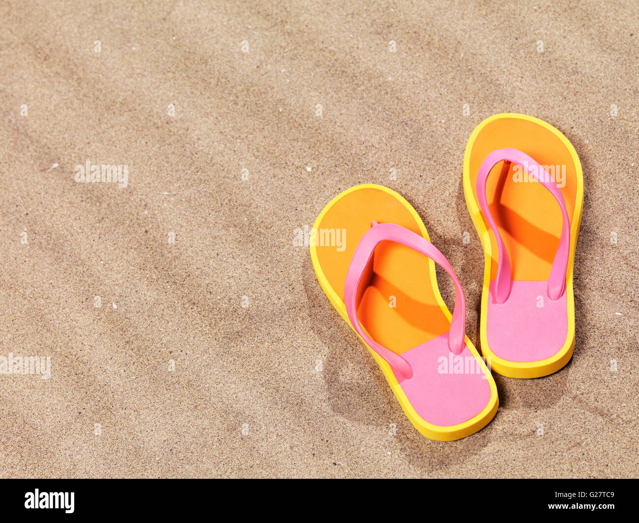 Une paire de tongs rose-orange allongé sur le sable Banque D'Images