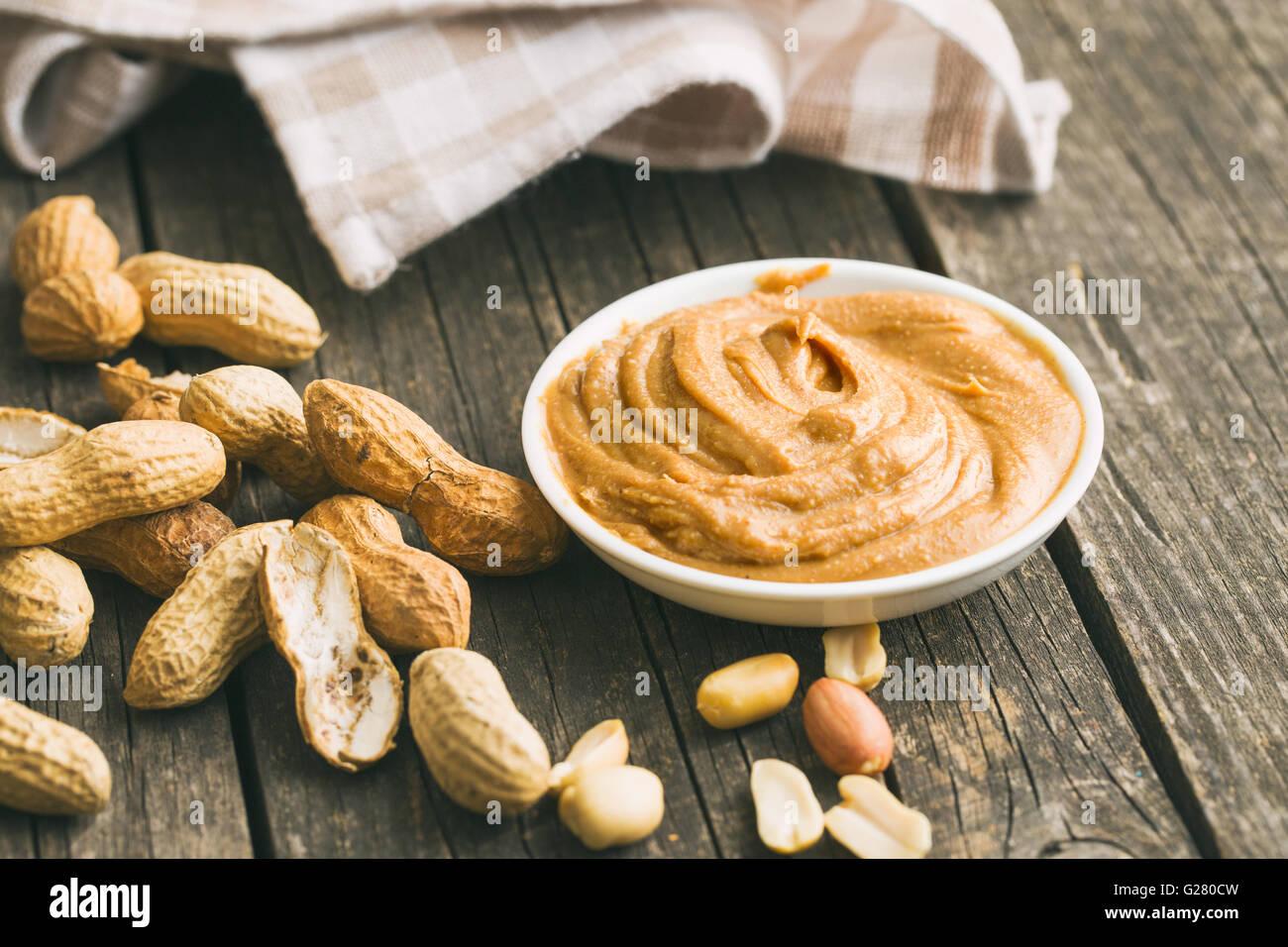 Le beurre d'arachide crémeux et les arachides. Tartiner de beurre d'arachides dans le bol. Photo Stock