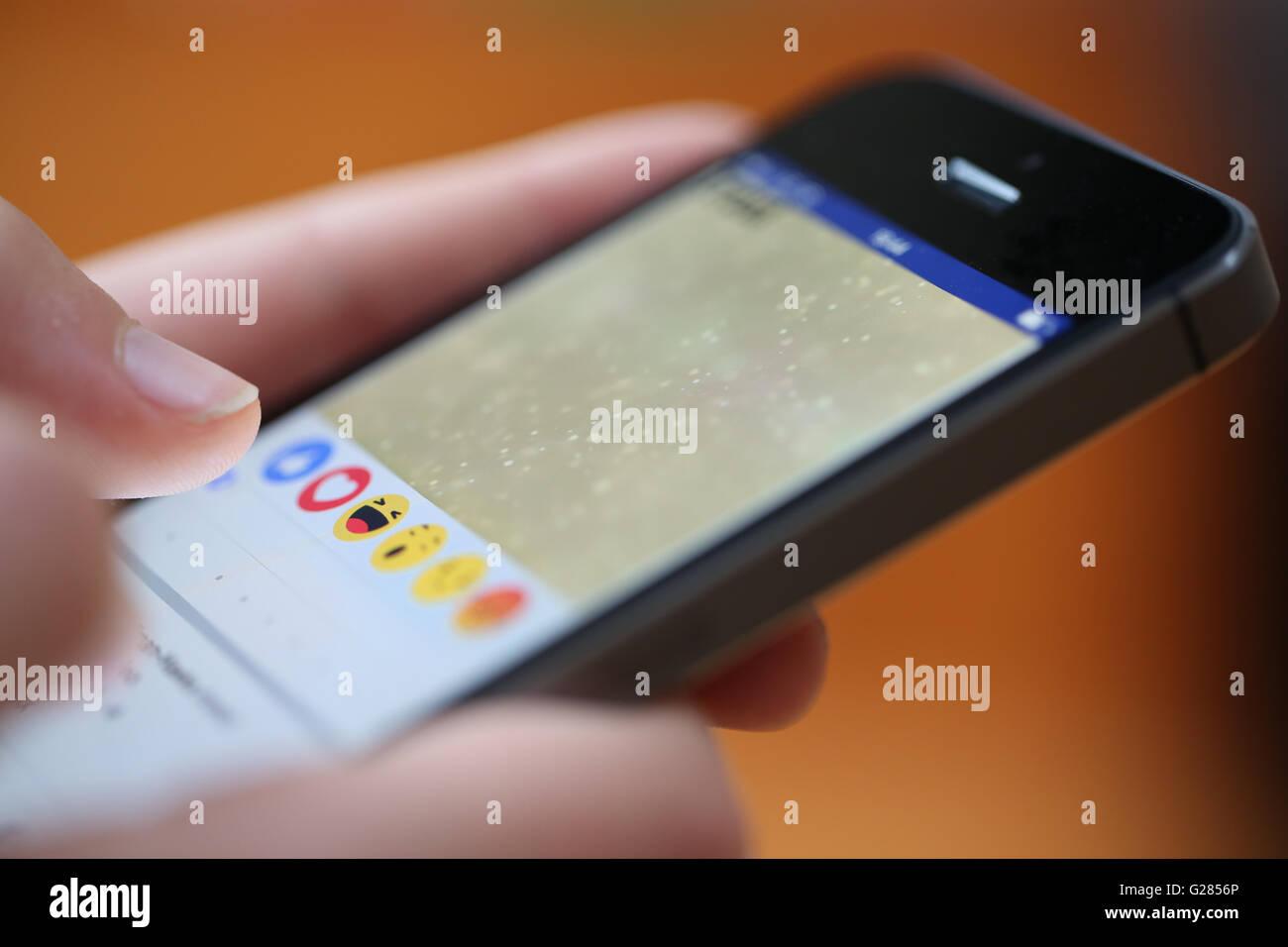 Un adolescent à l'aide de réactions sur l'application facebook sur un téléphone intelligent Photo Stock