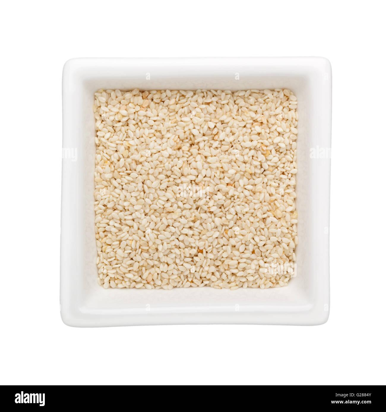 Graines de sésame blanches dans un bol carré isolé sur fond blanc Photo Stock