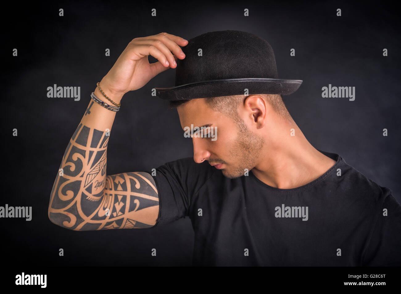0b2131bc9374b Beau et élégant jeune homme avec chapeau melon noir et t-shirt. Tatouages  frais sur les armes, le profil Voir