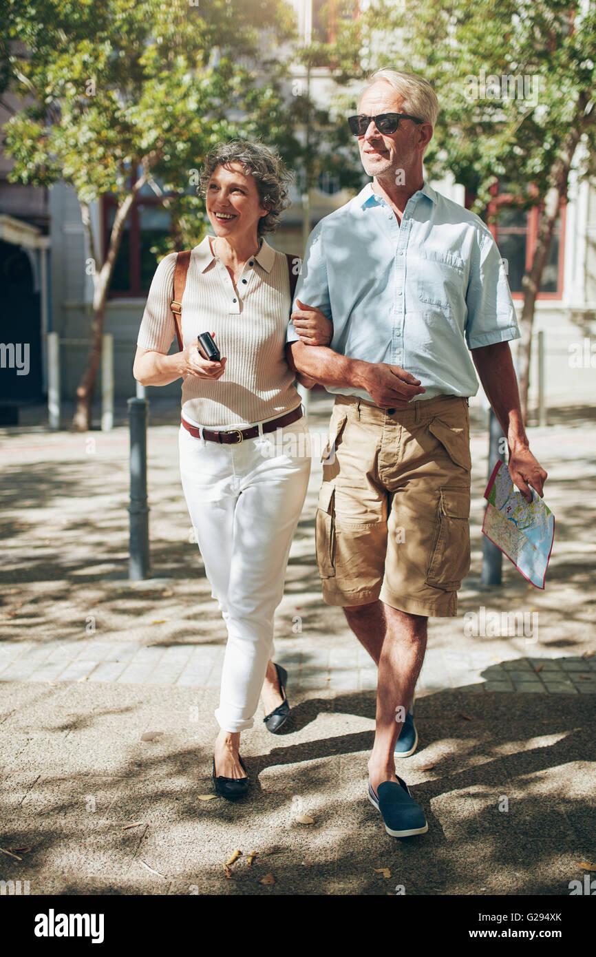 Mature couple walking autour de la ville avec une carte. Happy senior man and woman on a vacation. Photo Stock